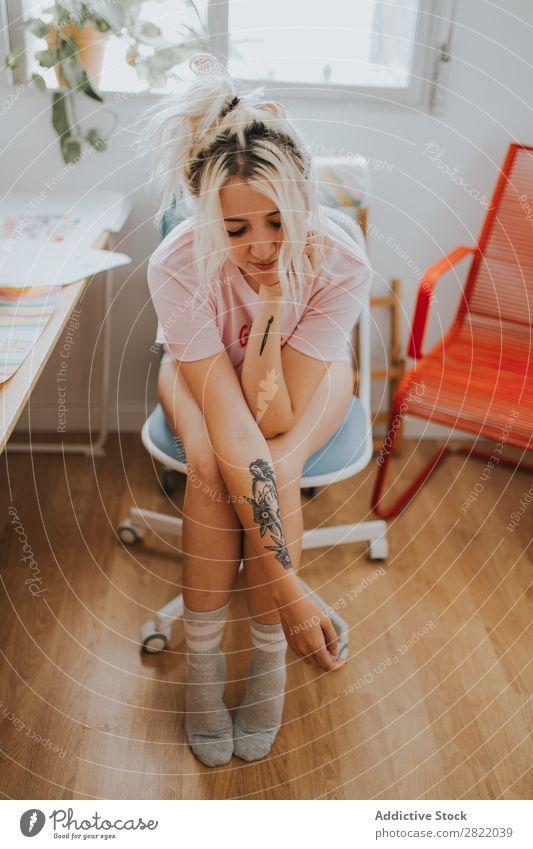 Hübsche Frau sitzt auf einem Stuhl. hübsch attraktiv heiß verführerisch Tattoo sitzen Arme Augen geschlossen Arbeitsplatz Glück schön Jugendliche