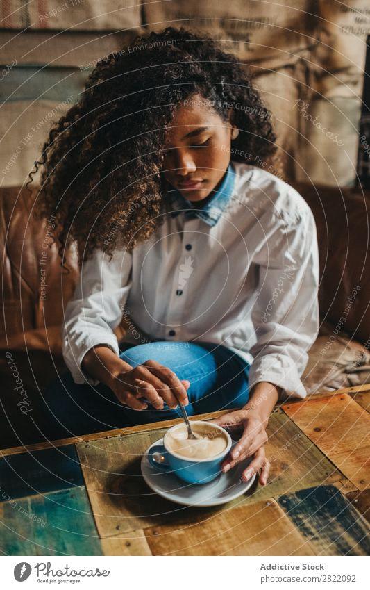 Ethnische Frau, die eine Tasse Kaffee rührt. hübsch schön urwüchsig schwarz lockig Jugendliche rühren Latte brünett attraktiv Mensch Beautyfotografie Erwachsene