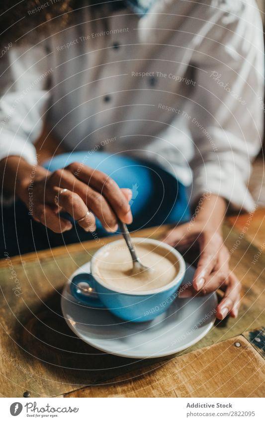 Getreidefrau, die eine Tasse Kaffee rührt. Frau schön urwüchsig schwarz Feldfrüchte Jugendliche Afrikanisch rühren Latte brünett attraktiv Mensch