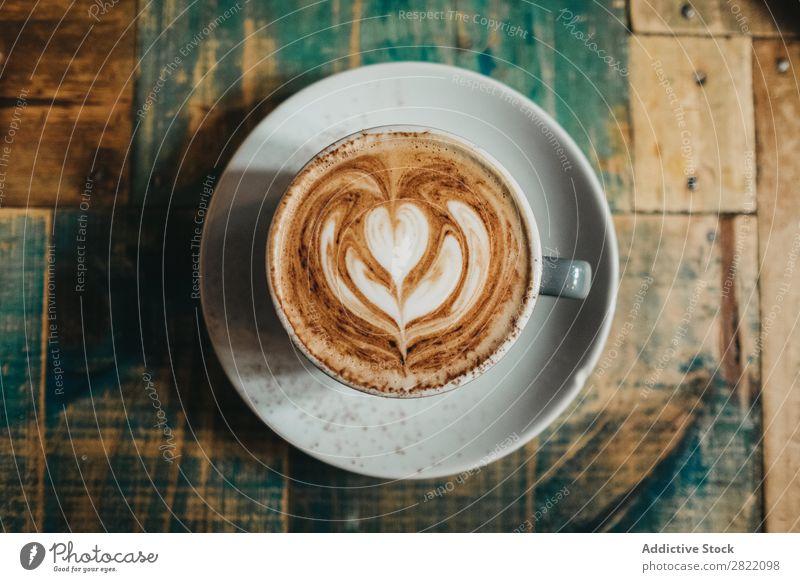 Tasse Latte mit Blume Kaffee Tisch trinken heiß braun Schaum Café Cappuccino Frühstück Becher Keramik blau Getränk Lebensmittel frisch Kunst Untertasse Holz