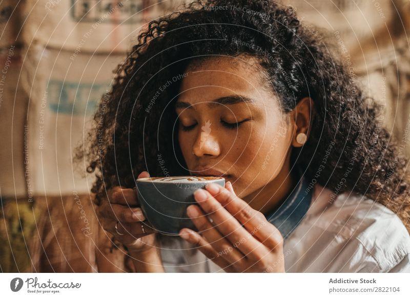 Frau trinkt eine Tasse Kaffee. schön urwüchsig schwarz Jugendliche Afrikanisch rühren Latte brünett attraktiv Mensch Beautyfotografie Erwachsene Stil niedlich