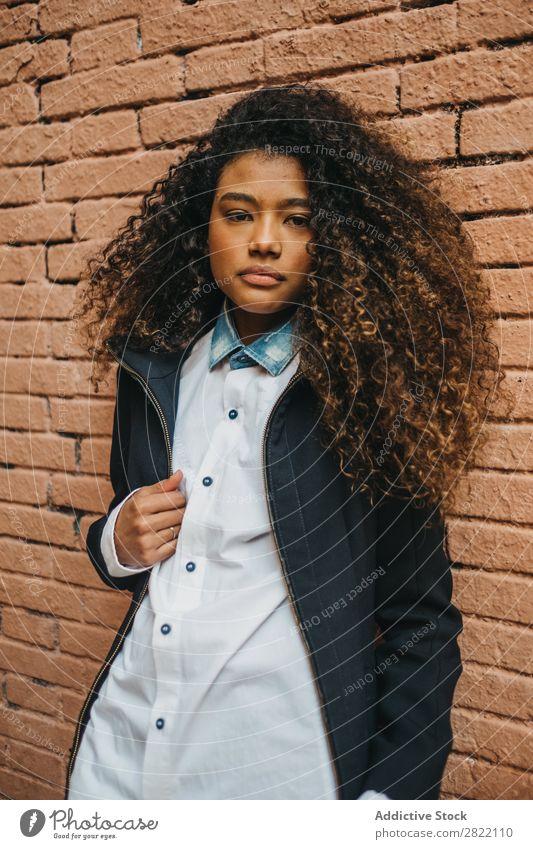 Stilvolle Frau an der Ziegelwand hübsch schön urwüchsig schwarz lockig Afrikanisch Jugendliche stehen Wand Backstein Straße brünett attraktiv Mensch