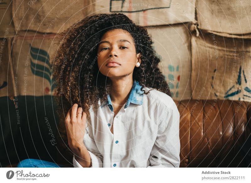 Stilvolle ethnische Frau auf der Couch hübsch schön urwüchsig schwarz lockig Jugendliche Leder Liege Sofa braun sitzen Blick in die Kamera brünett attraktiv