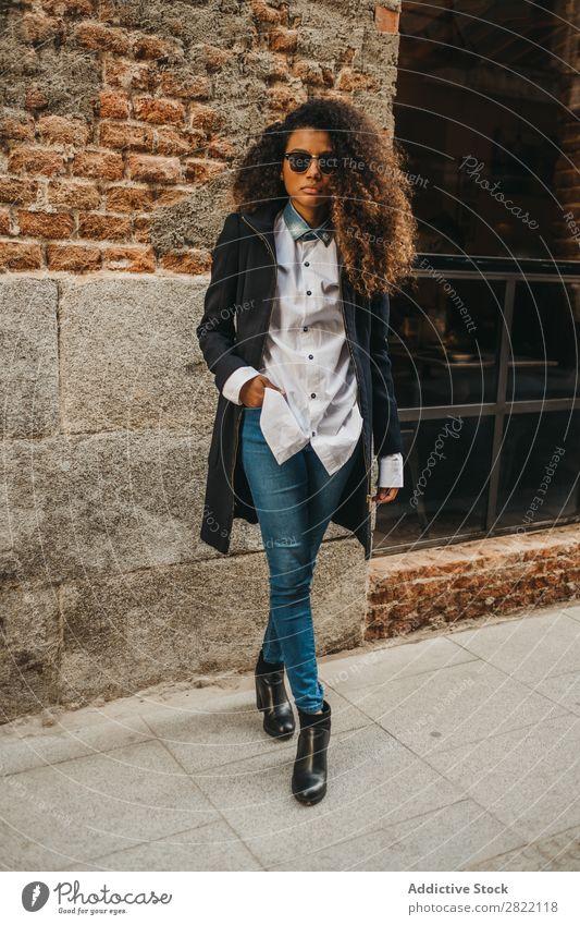Stilvolle Frau an der Ziegelwand hübsch schön urwüchsig schwarz lockig Afrikanisch Jugendliche stehen Wand Backstein Straße Sonnenbrille brünett attraktiv