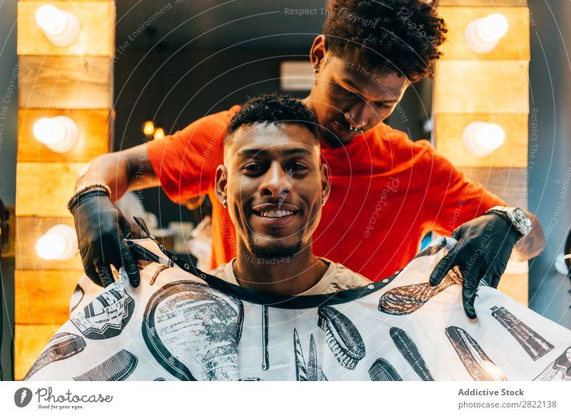 Fröhlicher Kunde im Friseursalon Haarkleid Behaarung Salon Umhang anmachend schwarz Mann Jugendliche Klient Haare schneiden Haare & Frisuren Fürsorge