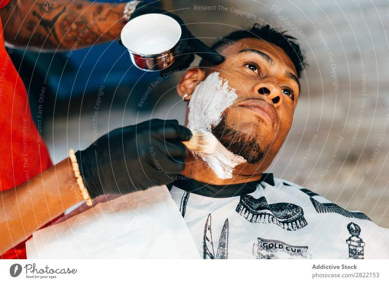 Friseur legt Schaum auf das Gesicht Friseursalon Kunde Haarkleid Behaarung Rasur Putten Salon schwarz Mann Jugendliche Klient Haare schneiden Haare & Frisuren
