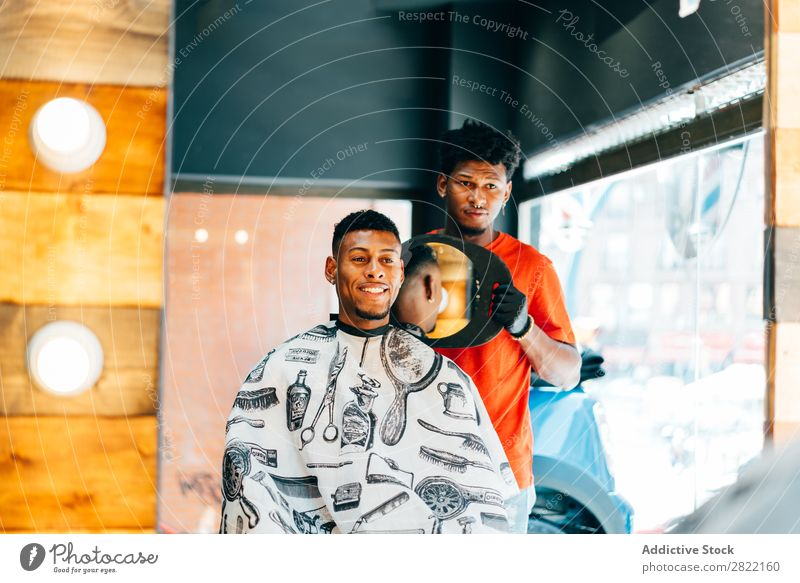 Friseur zeigt dem Kunden den Haarschnitt Friseursalon Haarkleid Behaarung zeigen Spiegel Reflexion & Spiegelung Salon schwarz Mann Jugendliche Klient