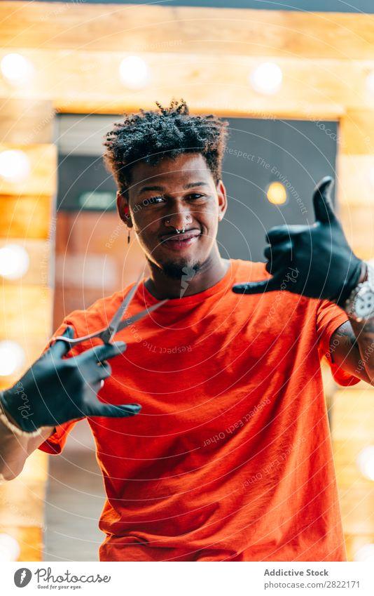 Gutaussehender Mann mit Schere Friseursalon Haarkleid Behaarung Salon Shaka Zeichen gestikulieren Blick in die Kamera schwarz Jugendliche Haare schneiden