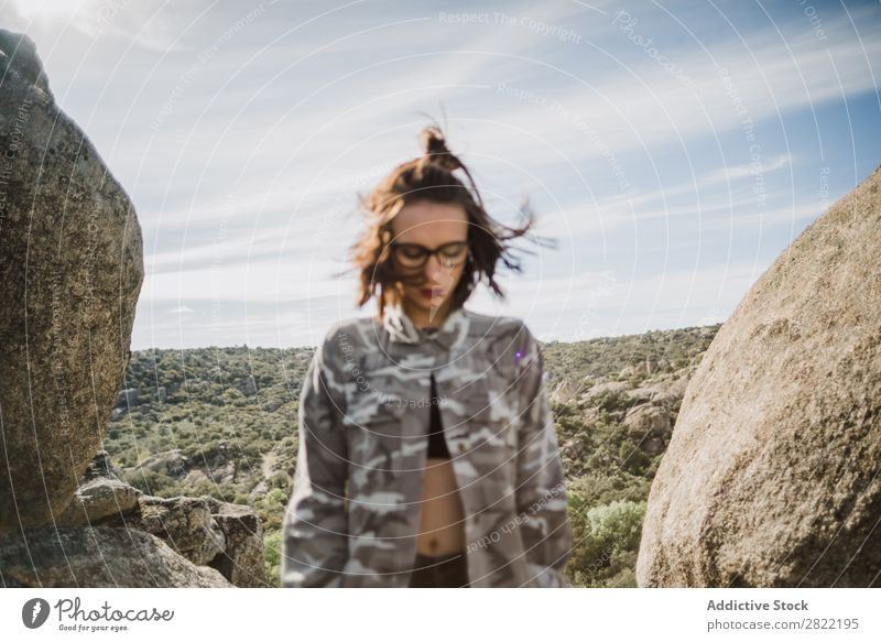 Hübsche junge Frau steht auf einer Klippe. Stil Natur Felsen Stein stehen Sonnenstrahlen Tag attraktiv schön Jugendliche Mode Schickimicki hübsch Coolness