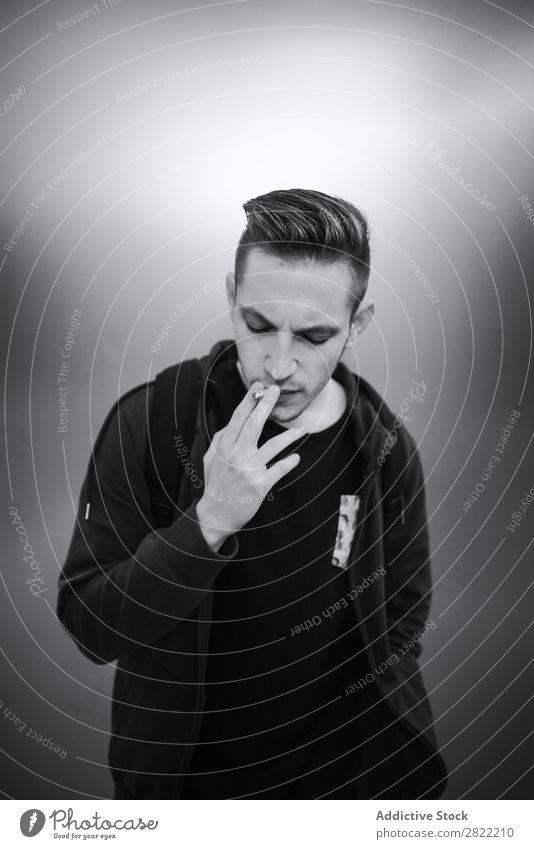Junger Mann raucht Zigarette Rauch Stil inhalieren Sucht Menschliches Gesicht Rauchmaschine Ausdruck Schwarzweißfoto schwarz Einatmen maskulin Tabak Porträt