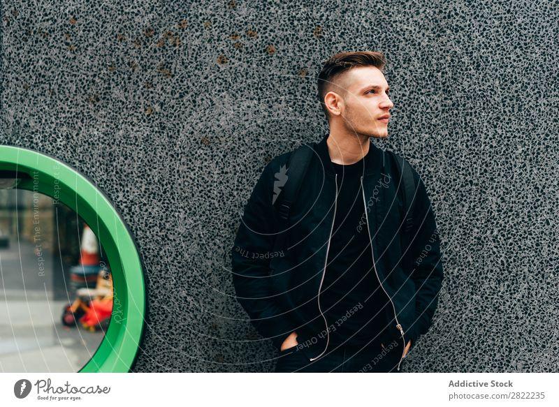 Junger Mann in Schwarz auf der Straße Reisender Stadt träumen London Stil England gutaussehend nachdenken Fürsorge Hände in den Taschen schwarz Jacke Wand