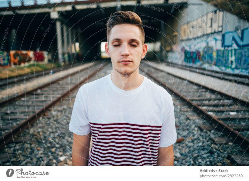 Junger Mann bei der Stadtbahn Eisenbahn heiter stehen Ferien & Urlaub & Reisen Graffiti Wand Verkehr Mensch Station Großstadt Jugendliche Lifestyle Ausflug