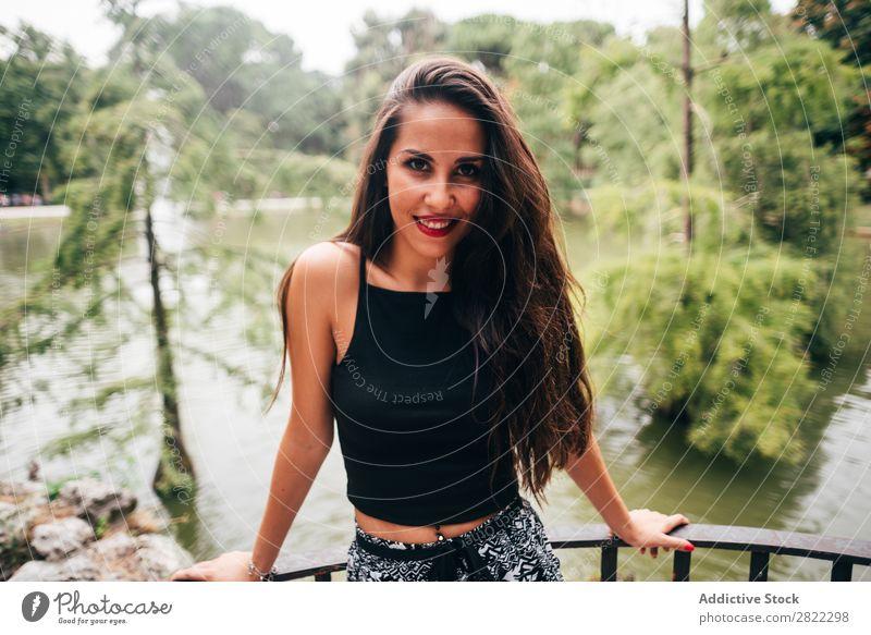 Brünette Frau, die sich auf den Handlauf am Fluss lehnt. hübsch Jugendliche schön brünett attraktiv Mensch Beautyfotografie Erwachsene Stil niedlich Lifestyle