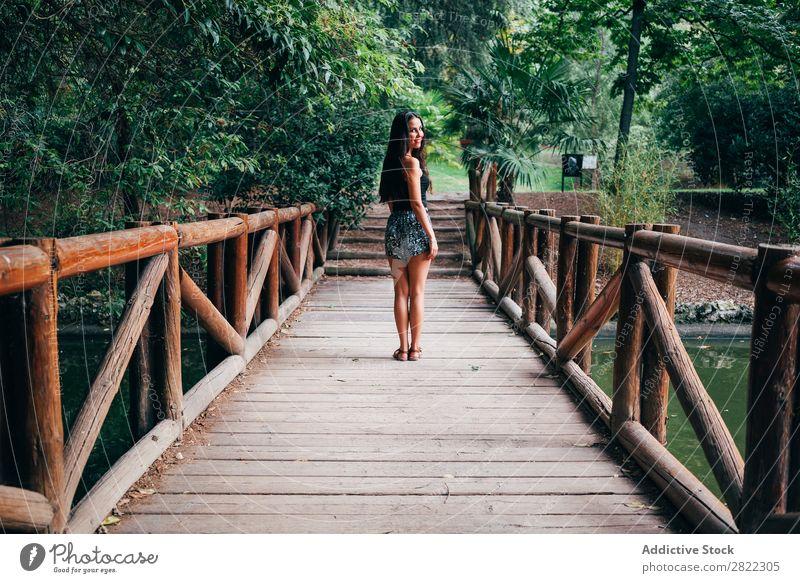 Junge Frau auf Holzbrücke hübsch Jugendliche schön Brücke stehen heiter Lächeln brünett attraktiv Mensch Beautyfotografie Erwachsene Stil niedlich Lifestyle