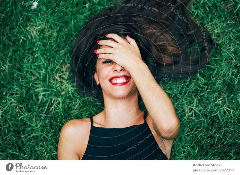 Fröhliche brünette Frau im Gras liegend hübsch Jugendliche schön heiter Lächeln lügen Natur Blick in die Kamera attraktiv Mensch Beautyfotografie Erwachsene