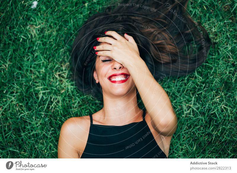 Fröhliche brünette Frau im Gras liegend hübsch Jugendliche schön heiter Lächeln lügen Natur attraktiv Mensch Beautyfotografie Erwachsene Stil niedlich Lifestyle