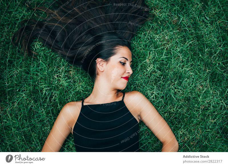Fröhliche brünette Frau im Gras liegend hübsch Jugendliche schön heiter lügen Natur attraktiv Mensch Beautyfotografie Erwachsene Stil niedlich Lifestyle Dame