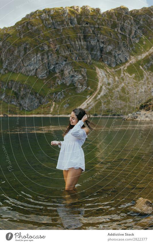 Hübsche Frau im Bergsee See Berge u. Gebirge Lächeln stehen Behaarung ausrichten berühren Hügel Halde Wasser Jugendliche Sommer Ferien & Urlaub & Reisen