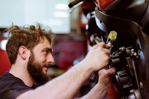 Mann, der am Fahrrad arbeitet Flugzeugwartung Detailaufnahme Teile u. Stücke Mitarbeiter Motorrad Werkstatt Mensch Verkehr Fahrzeug Garage benutzerdefiniert