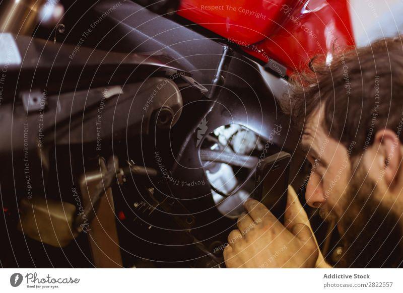 Mann benutzt Licht, um ins Fahrrad zu schauen. Mitarbeiter Mensch Blick inspizierend Motorrad Werkstatt geparkt Verkehr Fahrzeug Garage benutzerdefiniert