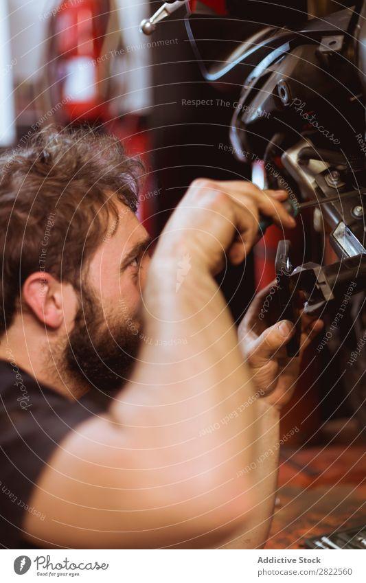 Person, die die Wartung des Fahrrads durchführt Mitarbeiter Mensch Blick inspizierend Motorrad Werkstatt geparkt Verkehr Fahrzeug Garage benutzerdefiniert