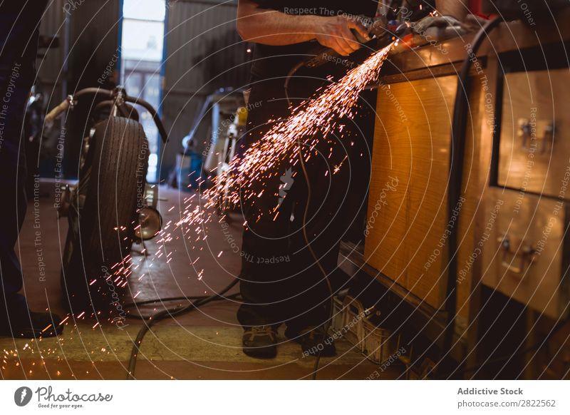 Nicht erkennbarer Arbeiter beim Schneiden von Metall in der Garage Motorrad Werkstatt geparkt Verkehr Mensch Funkelt Fahrzeug benutzerdefiniert