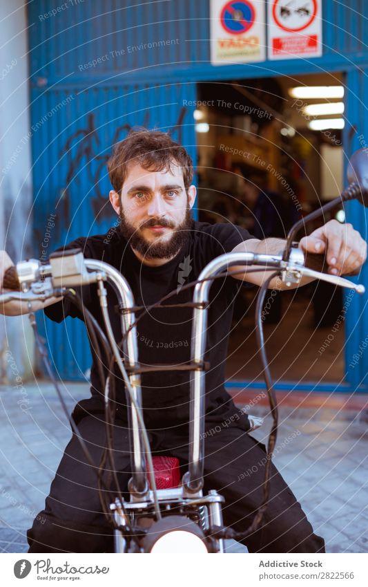 Mann auf dem Fahrrad in der Garage Motorradfahren Blick in die Kamera Porträt Mensch bärtig Werkstatt geparkt Verkehr Fahrzeug benutzerdefiniert