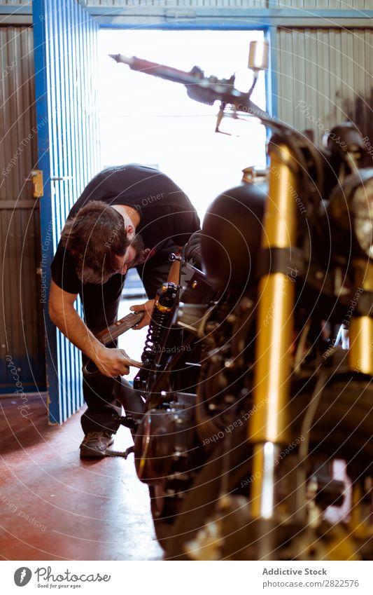 Mann, der in der Werkstatt am Fahrrad arbeitet. Mensch Flugzeugwartung Nahaufnahme Detailaufnahme Teile u. Stücke Hand Mitarbeiter Motorrad Verkehr Fahrzeug