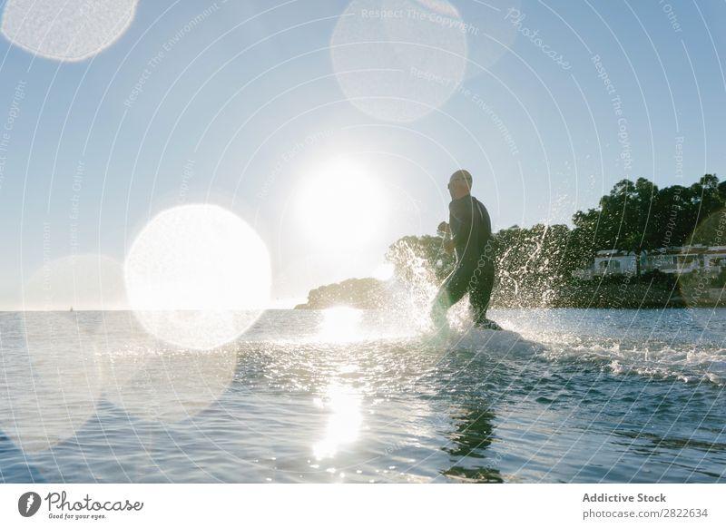 Taucher läuft ins Wasser Mann Neoprenanzug rennen Spritzer Bewegung Meer Freiheit Schwimmsportler Sportler Aktion Wassersport Freizeit & Hobby Erholung hell