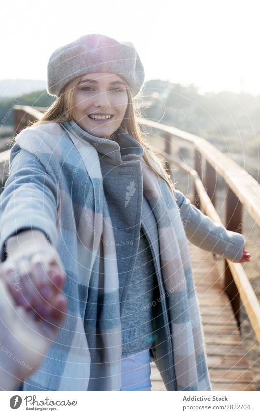 Stilvolle Frau hält die Hand des Fotografen. hübsch Jugendliche schön attraktiv Promenade Gang Holz Natur Baskenmütze mir folgen gestikulieren Mensch
