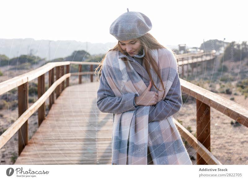Fröhliche Frau an der Promenade stehend hübsch Jugendliche schön attraktiv heiter Lächeln Gang Holz Natur Stil Baskenmütze Mensch Mantel Beautyfotografie