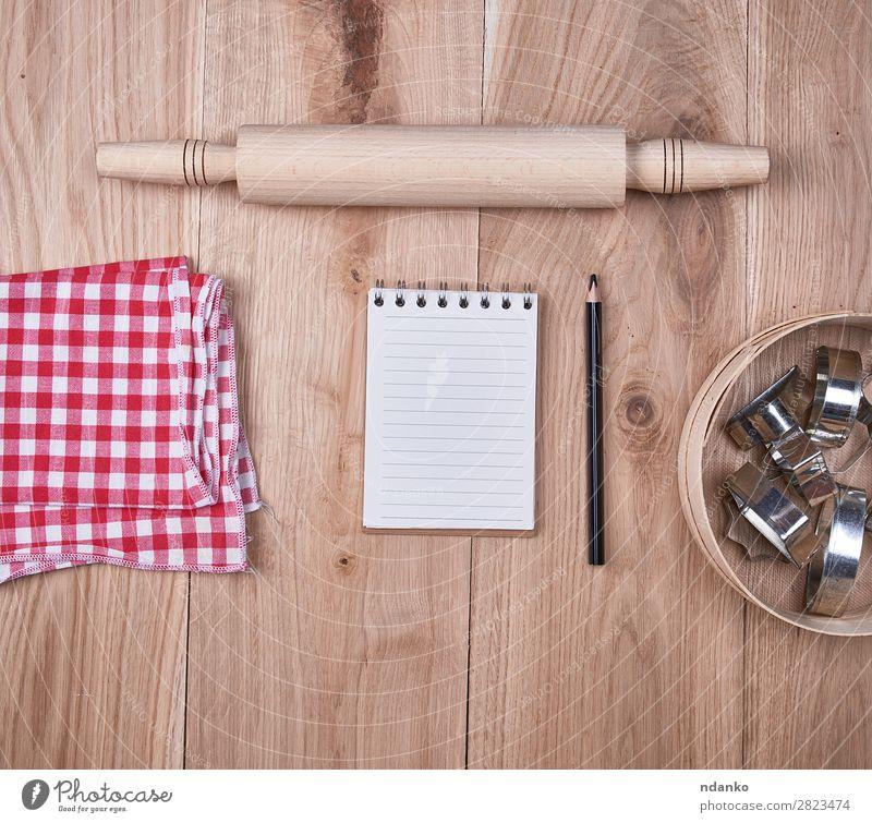 offenes Notizbuch in einer Zelle, rundes Holzsieb Besteck Tisch Küche Sieb Papier oben braun gelb rot Hintergrund blanko Essen zubereiten Textfreiraum leer