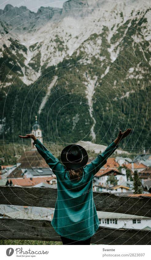 Frau steht vor der Bergstadt mit ausgestreckten Armen. Lifestyle Freude Ferien & Urlaub & Reisen Tourismus Abenteuer Sommer Berge u. Gebirge wandern feminin