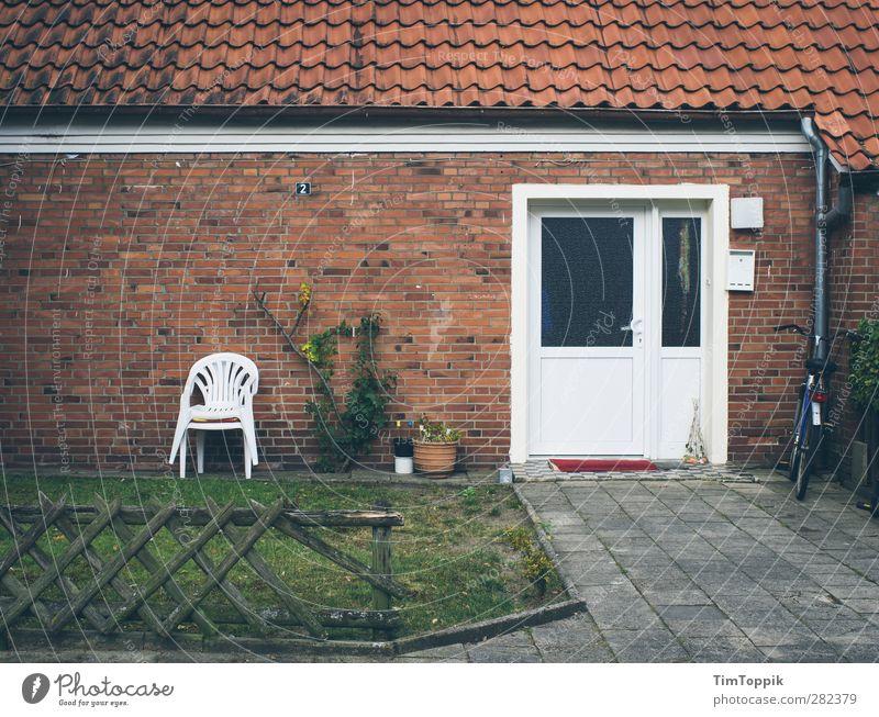 Verkehrsgünstig gelegen (mit Terrasse!) Haus trist Plastikstuhl Eingangstür Zaun Zaunpfahl schäbig Dach Backstein Backsteinwand Backsteinfassade Fahrrad Armut