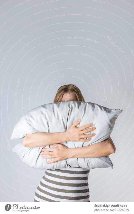 Junge Frau, die ein graues Kissen umarmt. Lifestyle schön Gesicht Wellness Erholung Schlafzimmer Mensch Erwachsene Arme Hand blond Streifen schlafen weinen dünn