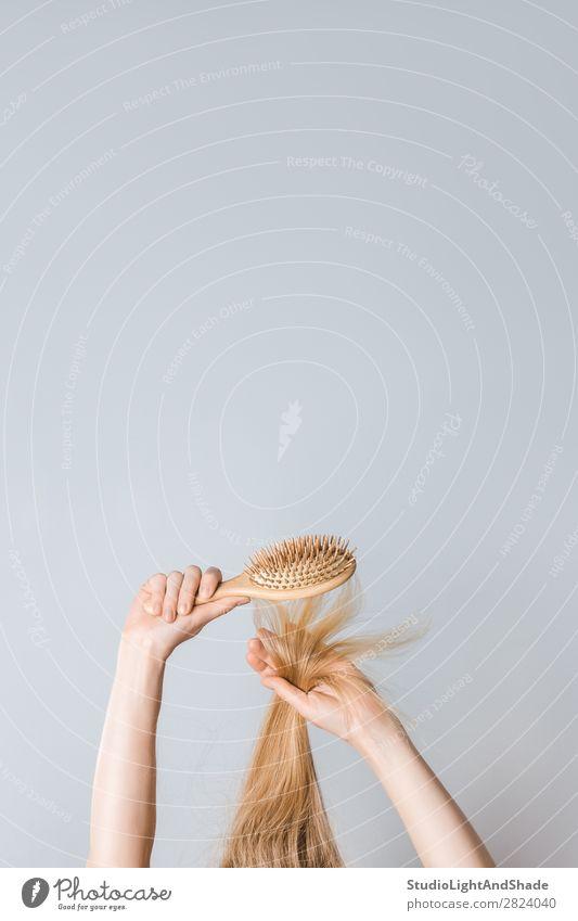 Blondes Haar mit einer Holzhaarbürste bürsten. Lifestyle schön Haare & Frisuren Gesundheitswesen Mensch Frau Erwachsene Arme Hand Mode blond Haarbürste lang