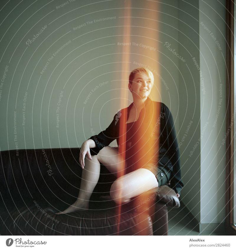 Junge Frau auf einem Sofa in einem analogen Bild mit Lightleaks Jugendliche Stadt schön Freude 18-30 Jahre Beine Erwachsene Leben feminin Stil Raum blond