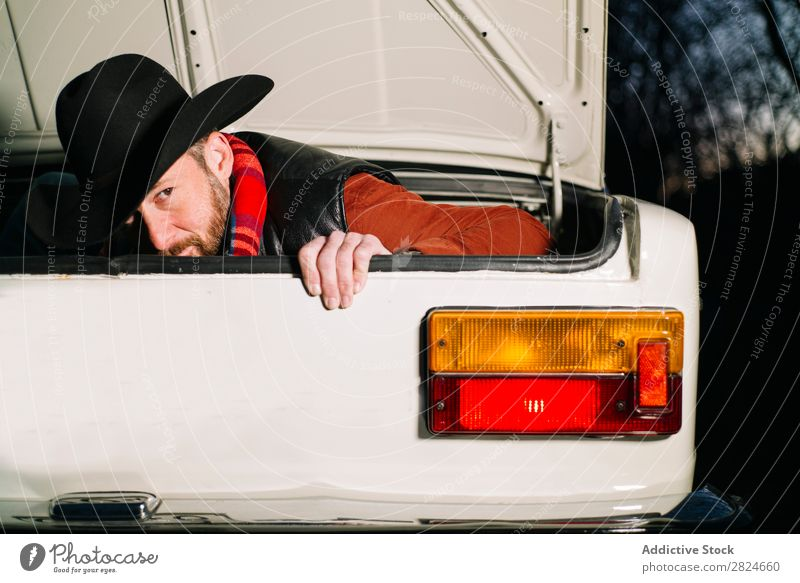 Mann im Kofferraum eines Oldtimers PKW altehrwürdig retro weiß Rüssel versteckend Hut Abend Fahrzeug klassisch Erwachsene Ferien & Urlaub & Reisen Mensch