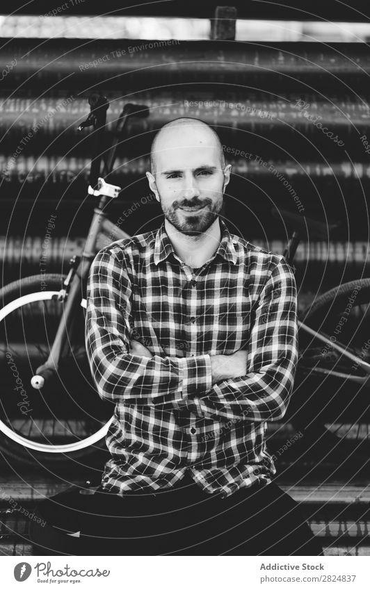 Gutaussehender haarloser Mann mit dem Fahrrad, der die Kamera mit gekreuzten Armen ansieht. Mensch Porträt die Arme verschränkt Fahrradfahrer Schatten