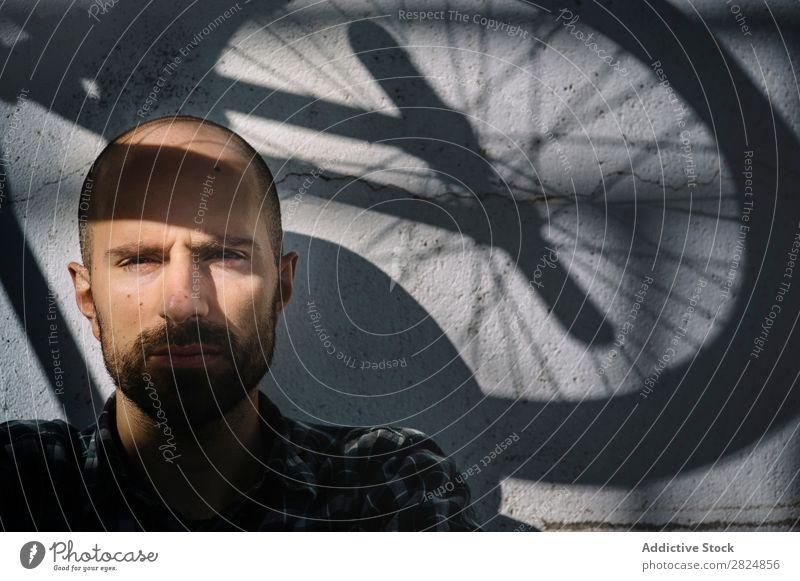 Ein Fahrradfahrer mit Radschatten Mensch Porträt Schatten Gesicht Mann Jugendliche Lifestyle Erwachsene Sport Freizeit & Hobby gutaussehend Blick in die Kamera