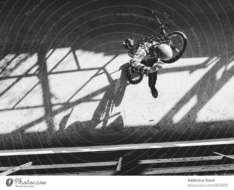 BMX-Fahrer mit Tricks Mann springen Fahrrad Sport Jugendliche Lifestyle in Bewegung Aktion extrem Schwarzweißfoto Reiter Motorradfahren üben Raser Freestyle