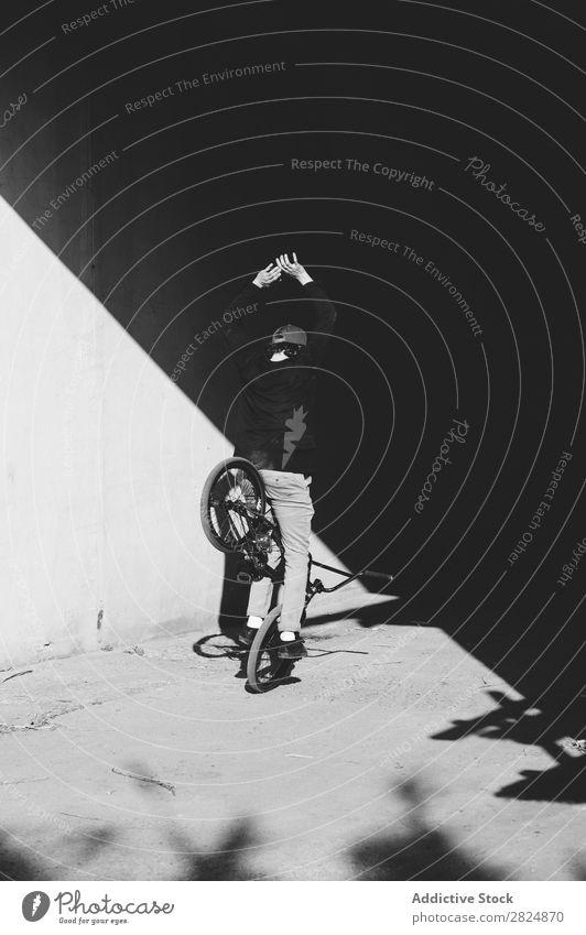 BMX-Fahrer steht neben der Wand Mann Körperhaltung Fahrrad Sport Jugendliche Lifestyle Aktion extrem Schwarzweißfoto Reiter Motorradfahren üben stehen Raser