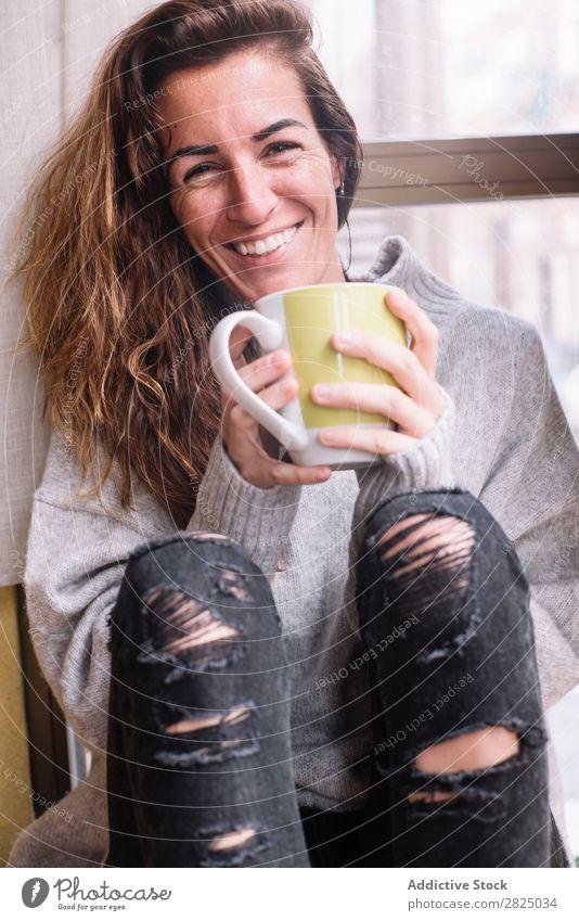 Fröhliche Frau entspannt sich bei einer Tasse. heimwärts Erholung Lifestyle Becher trinken heiß Lächeln Kaffee Tee schön Raum Mensch lässig Erwachsene Haus