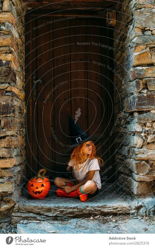 Liebenswertes Mädchen, das auf der Veranda posiert. Halloween so tun, als ob erschrecken Körperhaltung Porträt heiter Haus Kostüm Feste & Feiern Tradition
