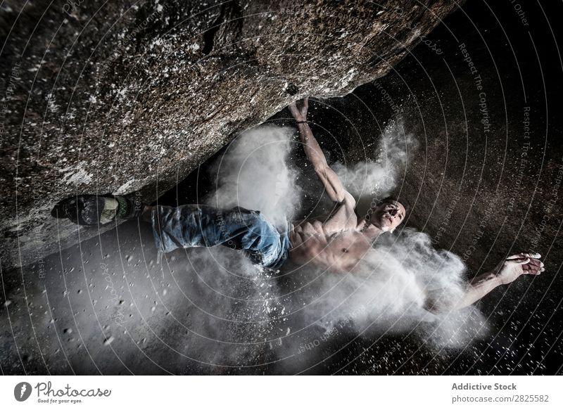 Ein Mann, der aus Magnesium auf den Felsen klettert, Berg in der Dämmerung. Kreativität Mensch Kreide Klettern stark sportlich Entscheidungen Energie Finger