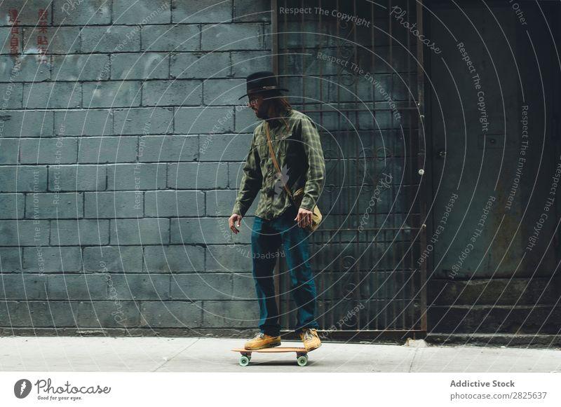 Mann fährt Skateboard in der Stadt Reiten Straße stehen Textfreiraum Coolness selbstbewußt Hut bärtig ernst brutal Vollbart Mensch Großstadt Schickimicki