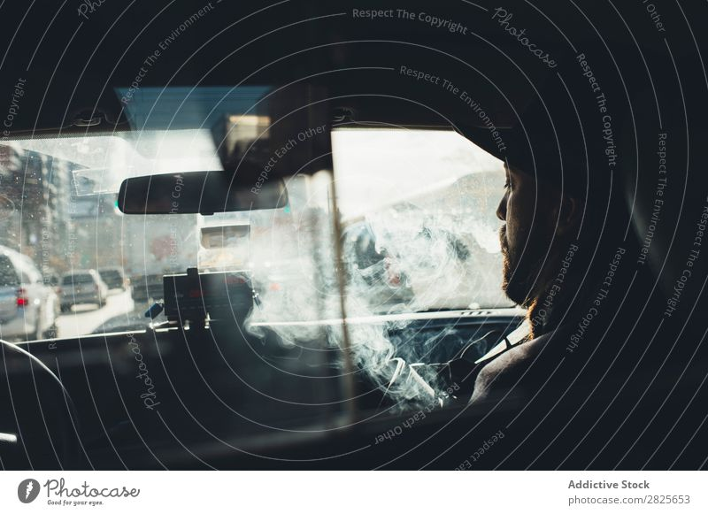 Mann im Auto sitzend Rauchen Taxi Fahrzeug Hut bärtig Zigarette selbstbewußt ernst Straße brutal Vollbart Mensch Großstadt Schickimicki Erwachsene lässig
