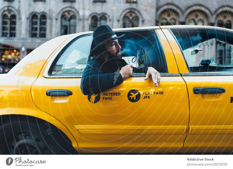Raucher sucht aus dem Taxi. Mann Rauchen Ausritt Fahrzeug Hut bärtig Zigarette selbstbewußt ernst Straße brutal Vollbart Mensch Großstadt Schickimicki