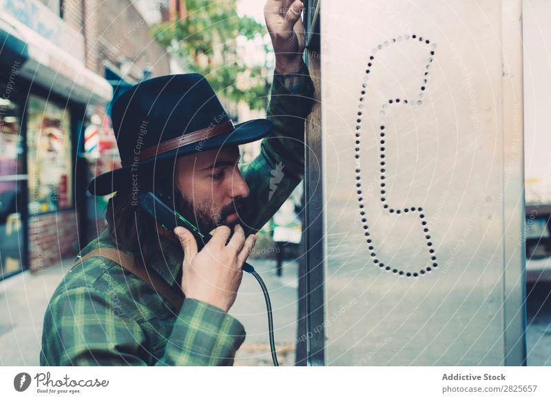 Gutaussehender Mann, der am Münztelefon spricht. Münzbehälter sprechen Telefongespräch Hut bärtig selbstbewußt ernst Straße brutal Vollbart Mensch Großstadt