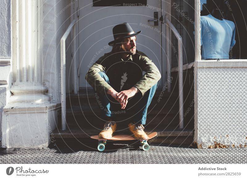 Cooler Mann auf der Treppe sitzend Coolness Skateboard selbstbewußt Hut bärtig ernst Straße brutal Vollbart Mensch Großstadt Schickimicki Erwachsene lässig